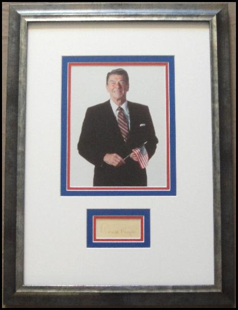 Ronald Reagan Holding an American Flag Display with Signature Cut in Red Ink